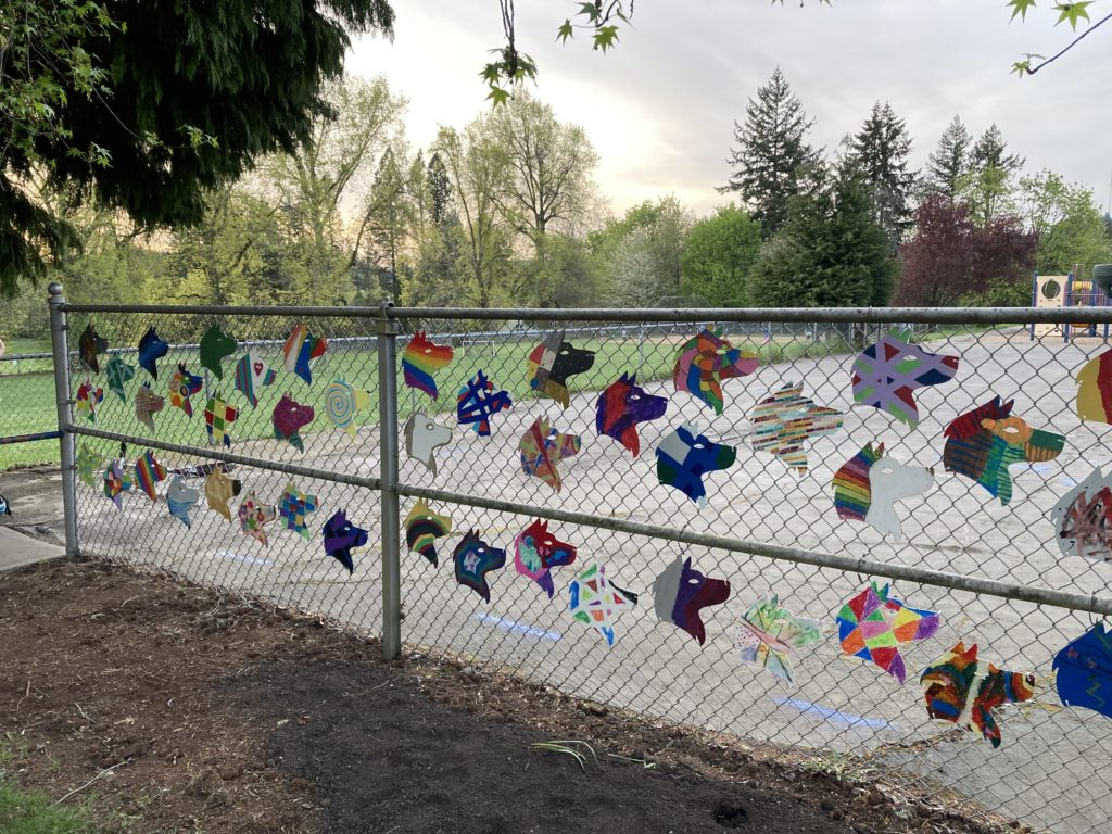 Student decorated Hayhurst Husky Heads hung on the fence in front of the school.